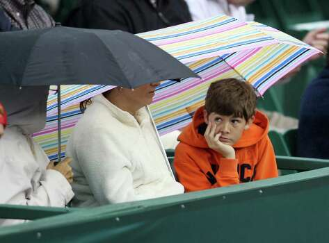 """Alec Osborne, 15, sits under the umbrella with his mom, Jennifer and friend Jan Kendall, during a rain delay during the doubles match between Bob and Mike Bryan and  Oliver Marach and Andre Sa, during the first round of the US Men's Clay Court Championships, Wednesday, April 10, 2013, in Houston.  Kendall said, """"We are hoping to keep our seats dry!"""" , when asked why they didn't seek shelter from the cold temperatures and rain. Photo: Karen Warren, Houston Chronicle / © 2013 Houston Chronicle"""