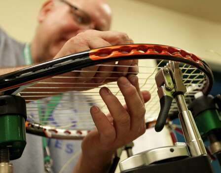 """Chuck Hakansson restrings a tennis racket for a player during a rain delay called during the doubles match between Bob and Mike Bryan and  Oliver Marach and Andre Sa, during the first round of the US Men's Clay Court Championships, Wednesday, April 10, 2013, in Houston. The drastic drop in temperatures caused a backlog of work for the """"stringers"""" at the tournament. Photo: Karen Warren, Houston Chronicle / © 2013 Houston Chronicle"""