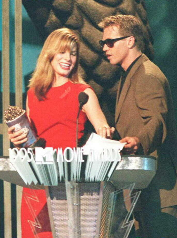 "Actress Sandra Bullock (L) receives her award in the most desirable female catagory from actor Val Kilmer during the 10 June taping of the 1995 MTV Movie Awards in Burbank, California. Bullock also won best on-screen duo with actor Keanu Reeves in the film ""Speed,"" which also won in the best action sequence category. Photo: Vince Bucci, AFP/Getty Images / AFP"