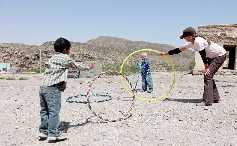 Crystal Allbright, 51 of Terlingua, (right) plays with Guillermo Gonzalez Luna, 4, (left) and Derian Diaz Luna, 4, Wednesday April 10, 2013 in Boquillas del Carmen, Mexico. Photo: Edward A. Ornelas, San Antonio Express-News / © 2013 San Antonio Express-News
