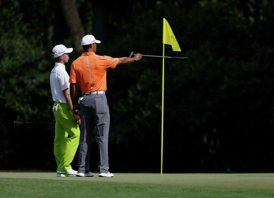 Guan Tianlang, the 14-year-old from China who is the youngest player in Masters history, goes to the right place for some advice on the greens at Augusta as four-time champion Tiger Woods gives a pointer on No. 11. Photo: Darron Cummings, STF / AP