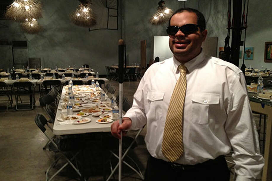 A server at The Blind Cafe in a dining room.