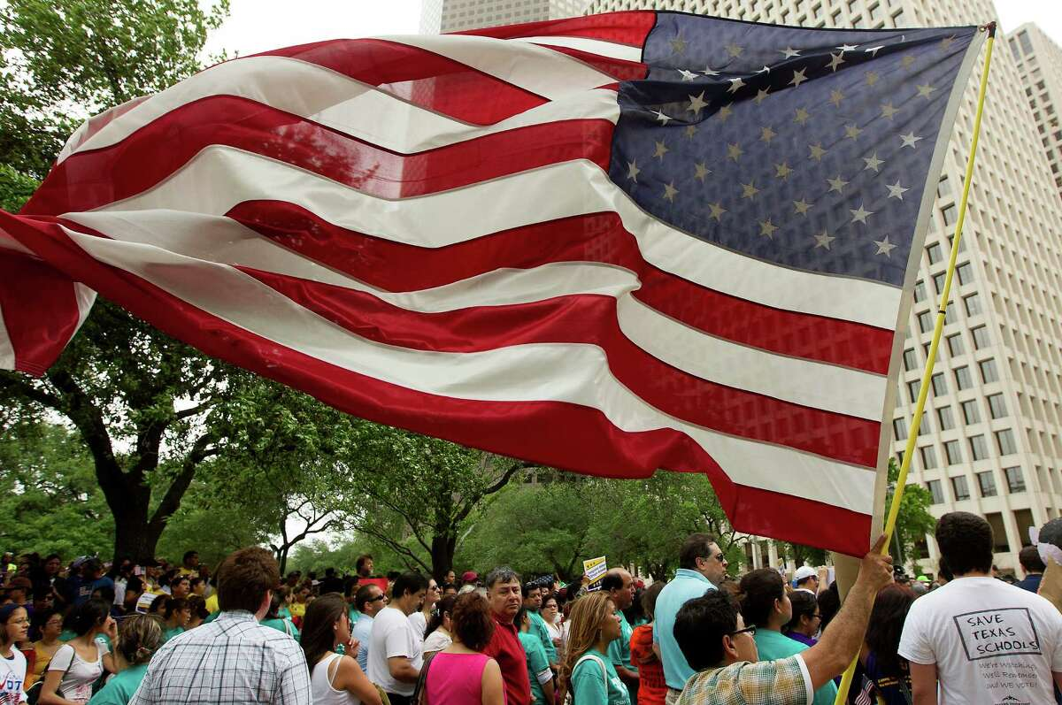 An American Flag is waved as hundreds of protesters marched along Smith St. to call on Texas Senator Ted Cruz to support immigration reform with a clear path to citizenship on Wednesday, April 10, 2013, in Houston. At the end of a march, the participants delivered 7,600 letters to Senator Cruz' Houston office.