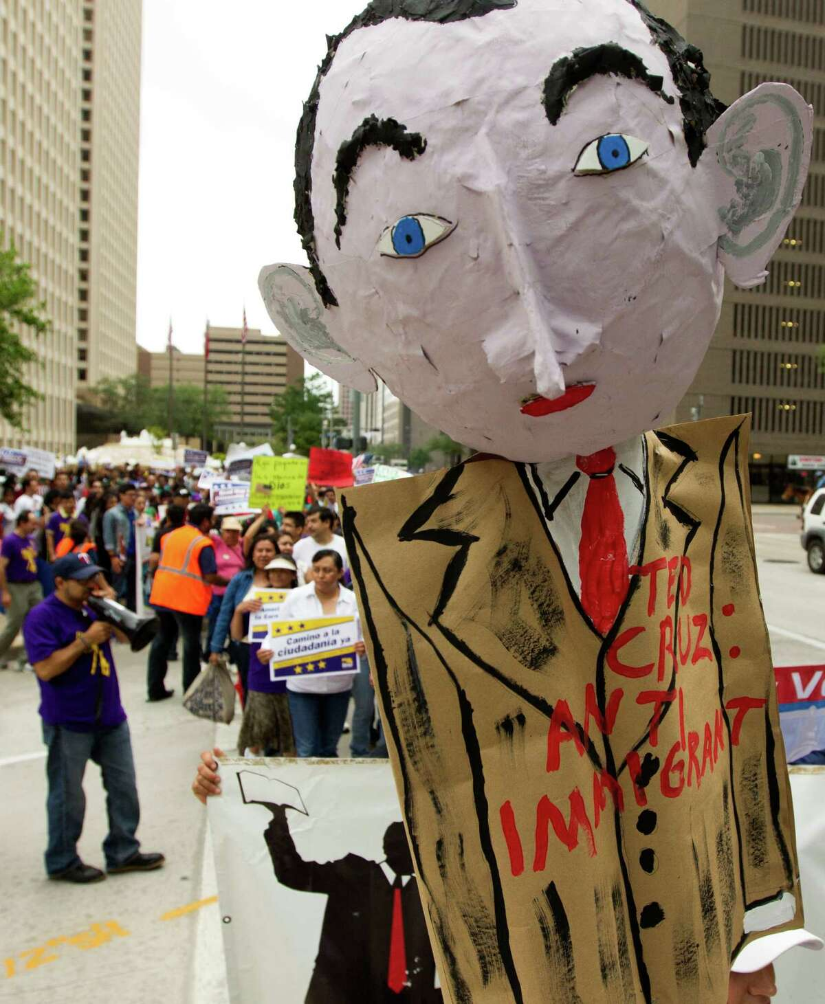 A paper mache doll of Ted Cruz is held up as hundreds of protesters marched along Smith St. to call on the Texas Senator to support immigration reform with a clear path to citizenship on Wednesday, April 10, 2013, in Houston.