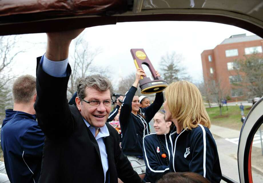 Connecticut head coach Geno Auriemma watches fans cheering his team as they ride a double-decker bus during a parade through campus, Wednesday,  April 10, 2013 in Storrs, Conn., honoring the team's NCAA women's college basketball championship. UConn defeated Louisville 93-60  in the championship game of the women's Final Four on Tuesday in New Orleans. (AP Photo/Jessica Hill) Photo: AP