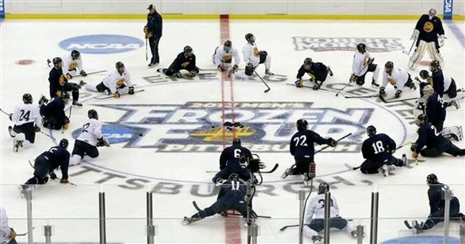 Quinnipiac players stretch at center ice during NCAA college hockey practice at the Consol Energy Center, Wednesday, April 10, 2013, in Pittsburgh. Quinnipiac is scheduled to play St. Cloud State in a semifinal at the Frozen Four on Thursday. (AP Photo/Keith Srakocic) Photo: Keith Srakocic, AP / Associated Press