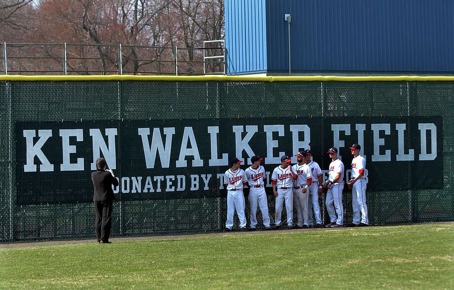 Foran High baseball seniors pose for photos in front of the new sign, which was unveiled at the end of a ceremony to rename Foran High's baseball field in honor of the late former coach Ken Walker on Wednesday in Milford, Conn. on Wednesday April 10, 2013. Photo: Christian Abraham / Connecticut Post