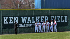 Foran High baseball seniors pose for photos in front of the new sign, which was unveiled at the end of a ceremony to rename Foran High's baseball field in honor of the late former coach Ken Walker on Wednesday in Milford, Conn. on Wednesday April 10, 2013.