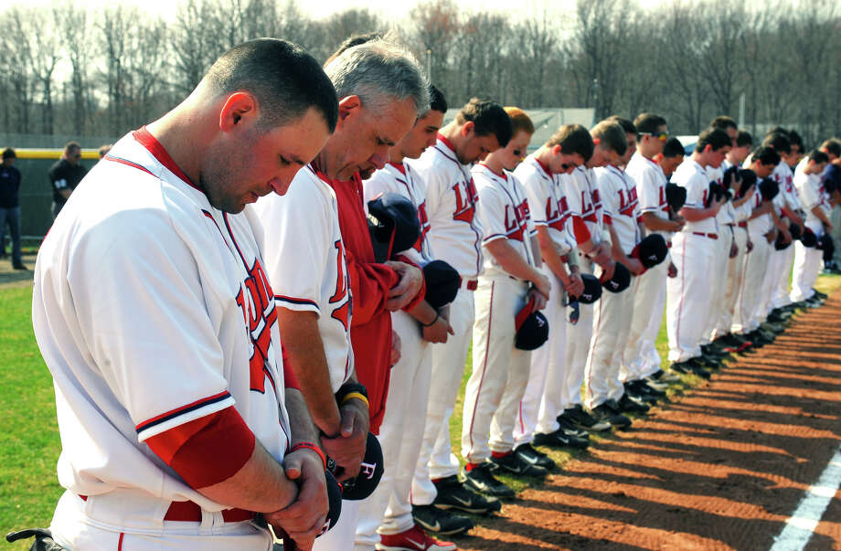 Foran High baseball coach Garret Walker, left, son of the late former coach Ken Walker, pauses with the rest of the team for a moment of silence, during a ceremony to rename Foran High's baseball field in honor of his father, Ken Walker, which was held before Wednesday's game against Jonathan Law in Milford, Conn. on Wednesday April 10, 2013. Photo: Christian Abraham / Connecticut Post