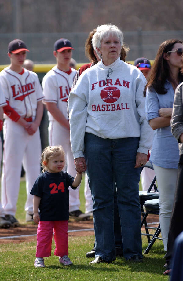 The sister of the late former coach Ken Walker, JoAnne Walker, stands with Ken's grandaughter Delaney, 2, during a ceremony to rename Foran High's baseball field in his honor, which was held before Wednesday's game against Jonathan Law in Milford, Conn. on Wednesday April 10, 2013. Photo: Christian Abraham / Connecticut Post