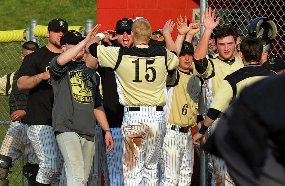 Jonathan Law's Jake Rouse, center, greets teammates after bringing in a run, during baseball action against Foran in Milford, Conn. on  April 10, 2013. Photo: Christian Abraham / Connecticut Post