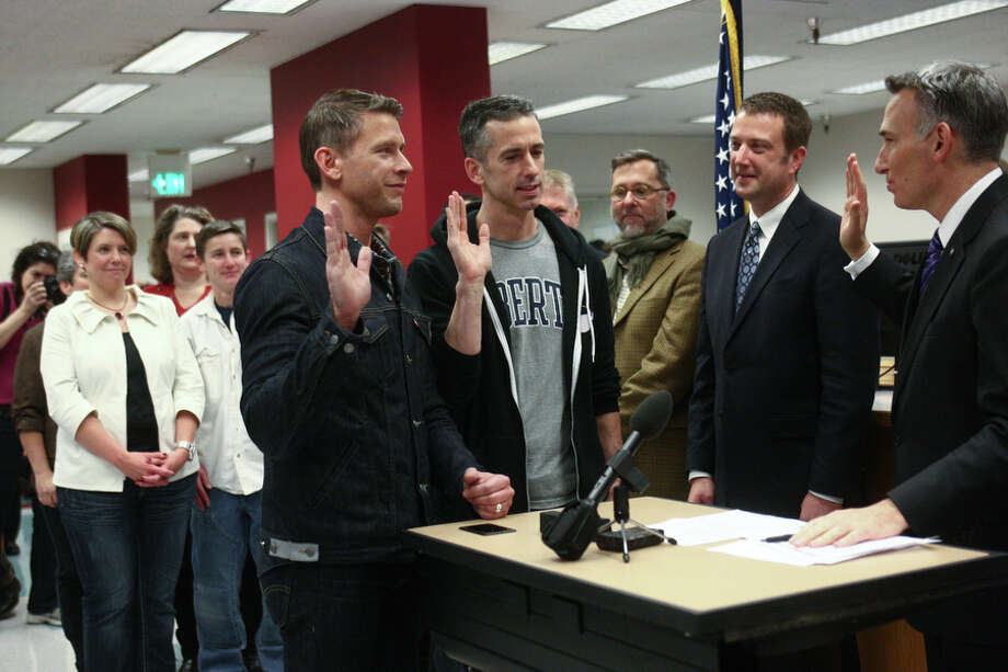 Same-sex advice columnist Dan Savage and his partner Terry Miller, left, take an oath that information provided is correct as they apply for their marriage license at the King County Administration Building on Thursday, December 6, 2012. Savage is a prominent gay rights activist. Photo: JOSHUA TRUJILLO, SEATTLEPI.COM / SEATTLEPI.COM