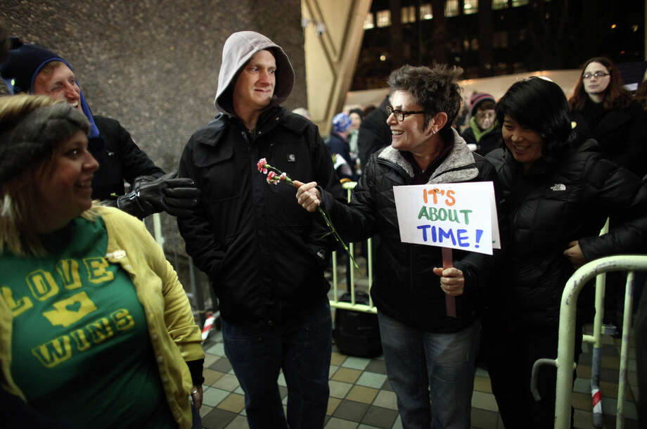 Junia Ribeiro holds a sign as she waits in line with her partner Patty Oh, right, outside of the King County Administration Building. Photo: JOSHUA TRUJILLO, SEATTLEPI.COM / SEATTLEPI.COM