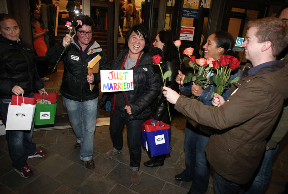 Junia Ribeiro, left, and her partner Patty Oh are greeted as the walk out of the King County Administration Building. Photo: JOSHUA TRUJILLO, SEATTLEPI.COM / SEATTLEPI.COM