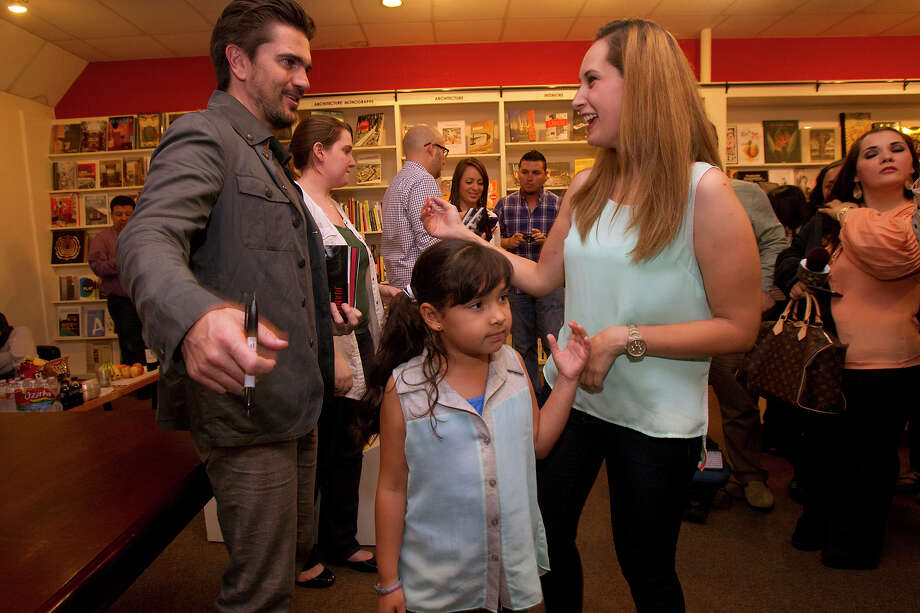 Colombian pop star Juanes, left, signs a book for a fan at the Brazos Book Store, Wednesday, April 10, 2013, in Houston. Photo: Cody Duty, Houston Chronicle / © 2013 Houston Chronicle