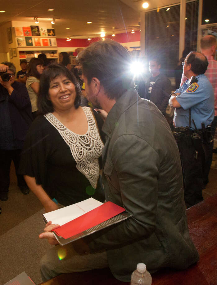 Colombian pop star Juanes, right, signs a book for a fan at the Brazos Book Store, Wednesday, April 10, 2013, in Houston. Photo: Cody Duty, Houston Chronicle / © 2013 Houston Chronicle