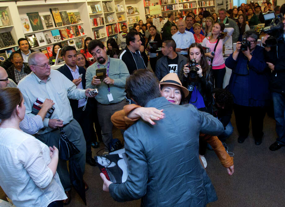 Colombian pop star Juanes, left, hugs Claudia Lopez, right, at the Brazos Book Store, Wednesday, April 10, 2013, in Houston. Photo: Cody Duty, Houston Chronicle / © 2013 Houston Chronicle