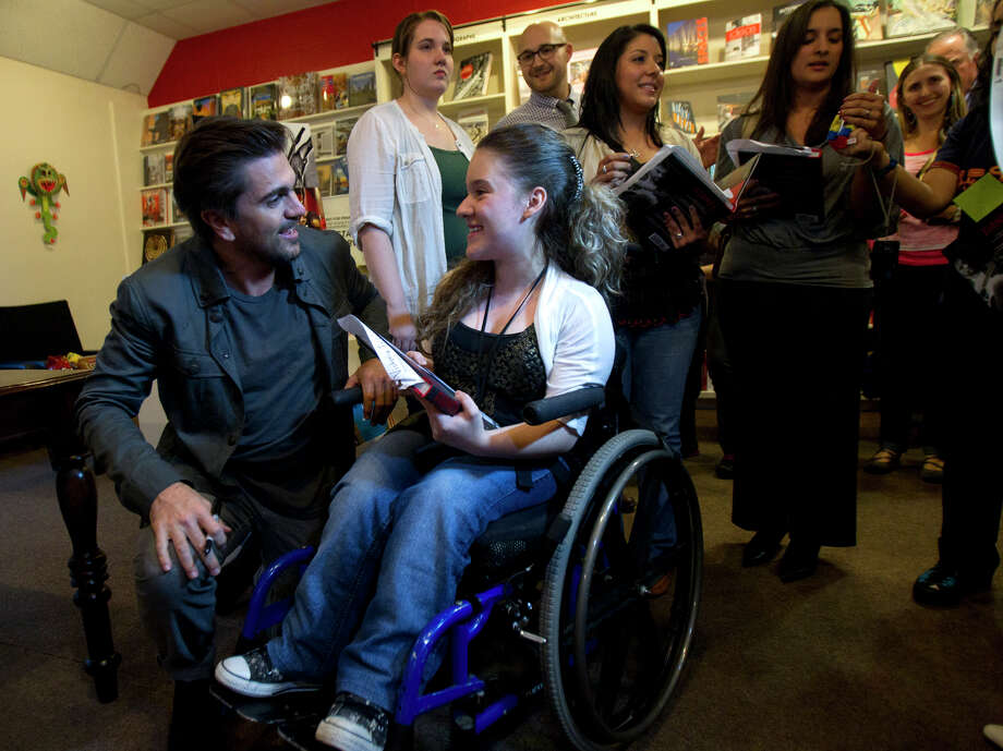 Colombian pop star Juanes, left, signs a book for Paulina Henao, 17, at the Brazos Book Store, Wednesday, April 10, 2013, in Houston. Photo: Cody Duty, Houston Chronicle / © 2013 Houston Chronicle
