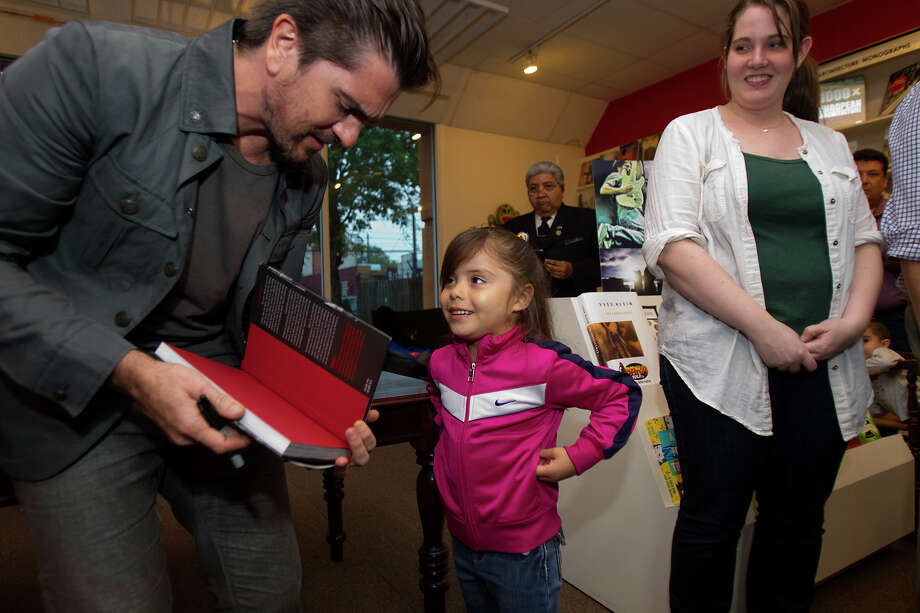 Colombian pop star Juanes, left, signs a book for Mia Ochoa, 4, at the Brazos Book Store, Wednesday, April 10, 2013, in Houston. Photo: Cody Duty, Houston Chronicle / © 2013 Houston Chronicle