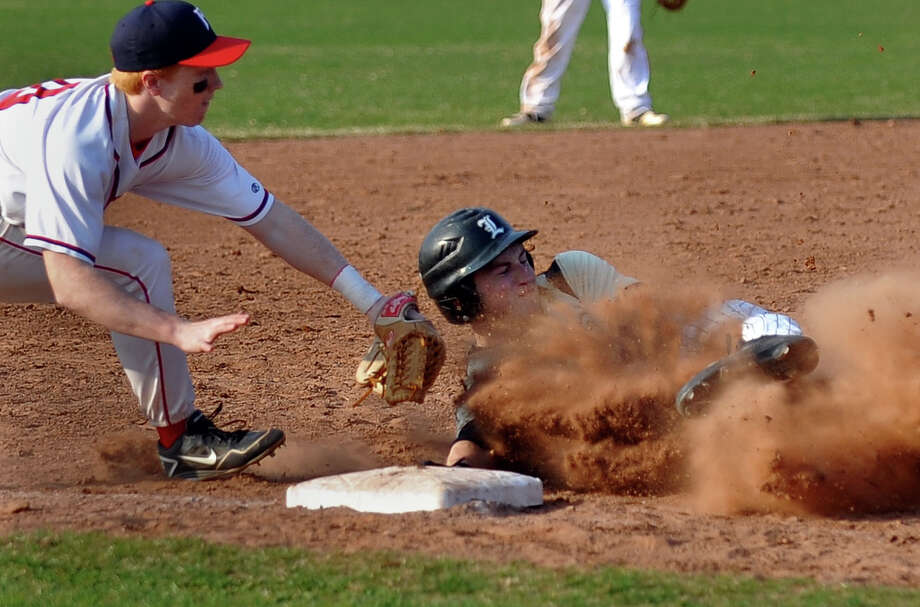Jonathan Law's #1 Tim Maher slides into third as Foran's Sam Olsson makes the tag, during baseball action in Milford, Conn. on  April 10, 2013. Maher was called out. Photo: Christian Abraham / Connecticut Post