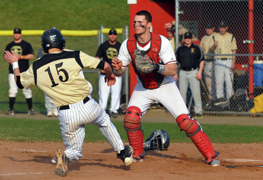 Foran catcher Joe Zanghi waits for the ball as Jonathan Law's Jake Rouse slides into home plate, during baseball action in Milford, Conn. on  April 10, 2013. Photo: Christian Abraham / Connecticut Post