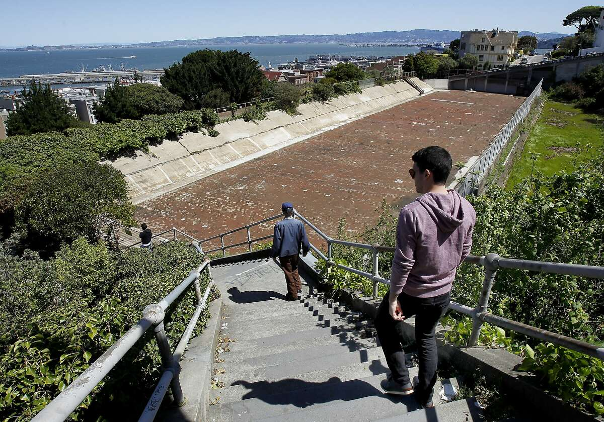 Pedestrians walks down the steep staircase next to the reservoir Monday April 8, 2013. The reservoir on Russian Hill in San Francisco, Calif. has not been used in many decades, and now neighbors and Supervisor Mark Farrell hope to revitalize the area and turn it into a park.