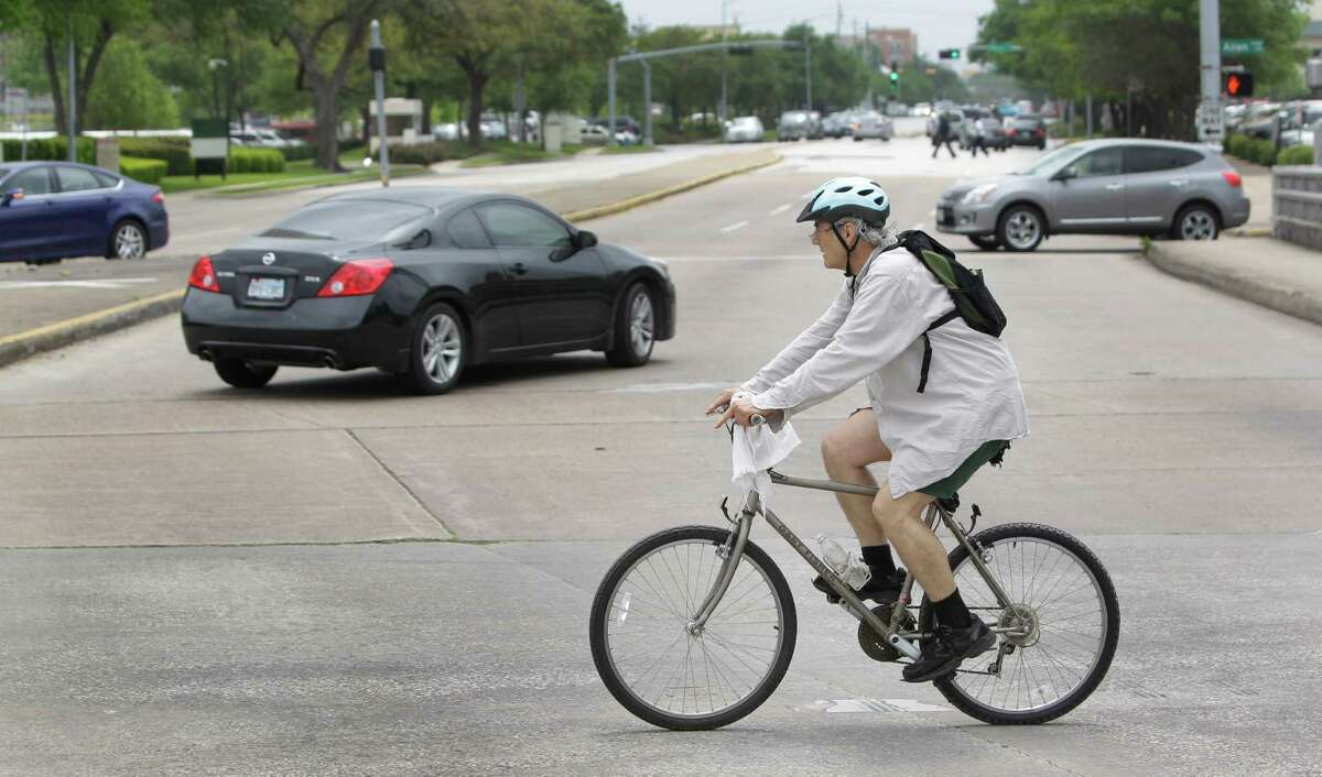 The intersection of Allen Parkway and Waugh on Wednesday illustrates the growing number of two-wheeled travelers in Houston. Gov. Rick Perry vetoed a 2009 bill to require drivers to keep a minimum distance from cyclists.