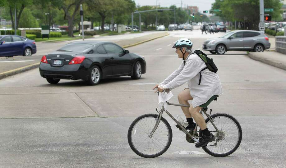 The intersection of Allen Parkway and Waugh on Wednesday illustrates the growing number of two-wheeled travelers in Houston. Gov. Rick Perry vetoed a 2009 bill to require drivers to keep a minimum distance from cyclists. Photo: Melissa Phillip, Staff / © 2013  Houston Chronicle