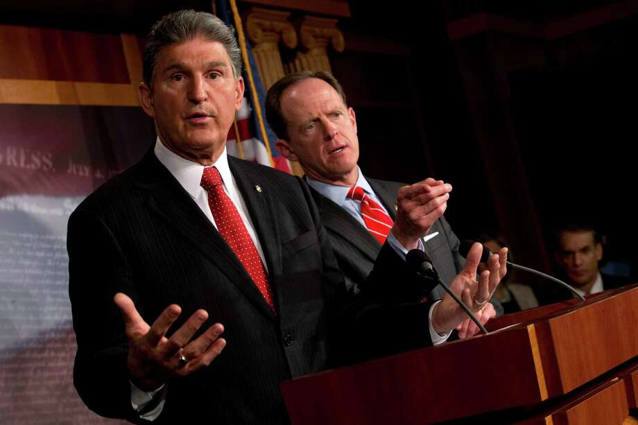 Sens. Joe Manchin (D-W.Va.), left, and Pat Toomey (R-Pa.) during a news conference on Capitol Hill in Washington, April 10, 2013. The two senators reached a bipartisan compromise on a measure to expand background checks for gun buyers Wednesday morning increasing the chances that a viable package of new gun safety laws will soon hit the Senate floor. (Doug Mills/The New York Times) Photo: DOUG MILLS / NYTNS