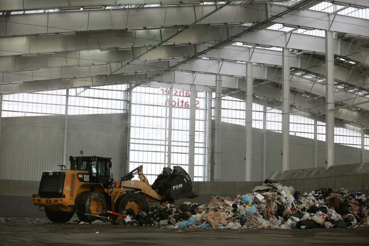 A tractor pushes unloaded trash in the new South Transfer Station.