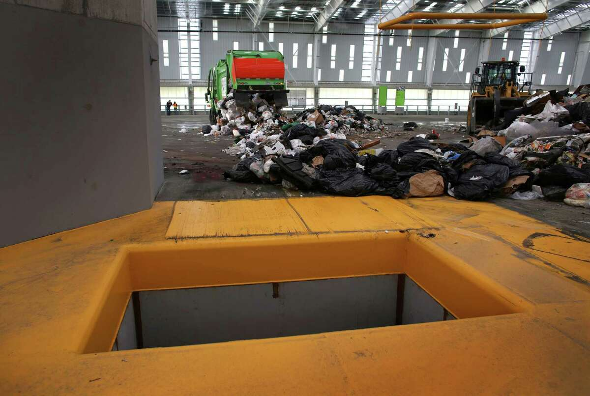 A garbage truck offloads trash, which is then pushed into the pit in the foreground at the new South Transfer Station. It then falls into a container below.