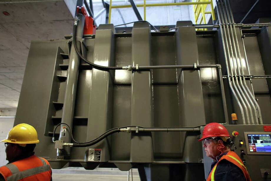 Trash pushed through openings in the main floor falls into a container where it is then compacted at the new South Transfer Station. Photo: JOSHUA TRUJILLO, SEATTLEPI.COM / SEATTLEPI.COM