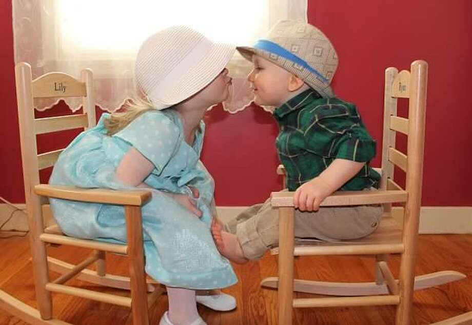 Lily, age 2, gives her year-old brother Ryan an Easter kiss. Grandma Brigid Rufo made Lily's dress and bought their Easter hats. They are the children of  Kate and Adam Cartier of Glenville. (Brigid Rufo)