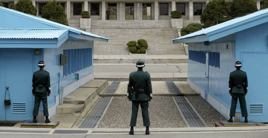 A North Korean soldier (background, top of the steps) looks at the southern side as South Korean soldiers stand guard at the border village of Panmunjom. North Korea might be preparing to launch its Musudan missile, believed to have a range of 2,175 miles. Photo: Lee Jin-man / Associated Press