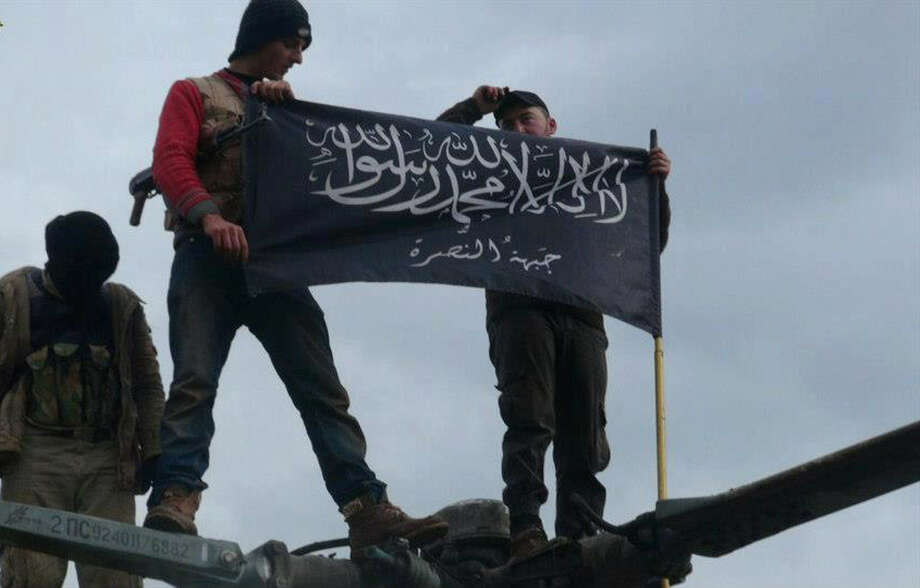Rebels from Jabhat al-Nusra, considered a terrorist group by the United States and now announced as joining forces with al-Qaida in Iraq, wave their brigade flag as they step on the top of a Syrian air force helicopter at the Taftanaz air base in Syria, captured by the rebels. Photo: Edlib News Network / Associated Press