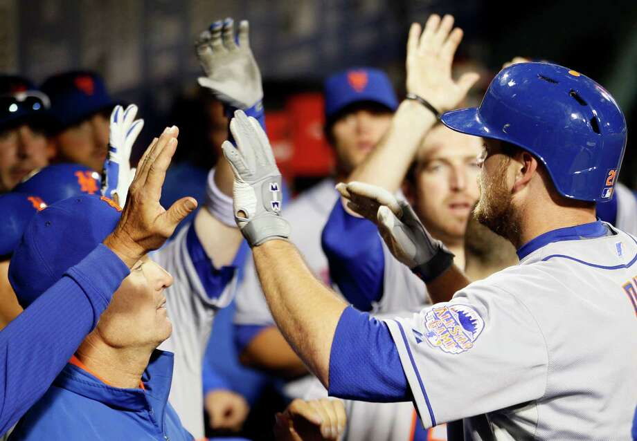 New York Mets' Lucas Duda returns to high-fives in the dugout after hitting a home run during the fourth inning of a baseball game against the Philadelphia Phillies on Wednesday, April 10, 2013, in Philadelphia. (AP Photo/Tom Mihalek) Photo: Tom Mihalek