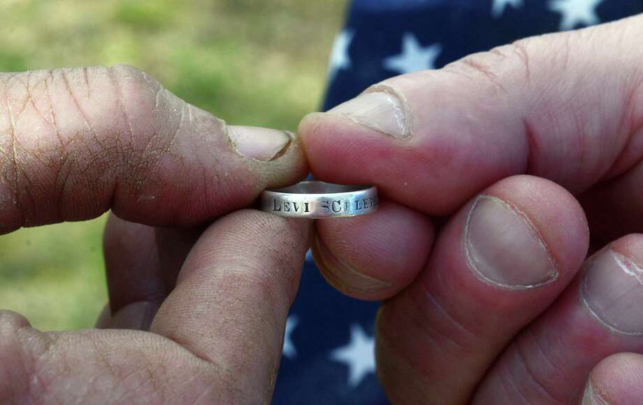 John Blue and Ernest Schlegel hold the ring bearing Civil War veteran Levi Schlegel's name, company and regiment during a ceremony in Reading, Pa. Photo: Susan L. Angstadt / Reading (Pa.) Eagle