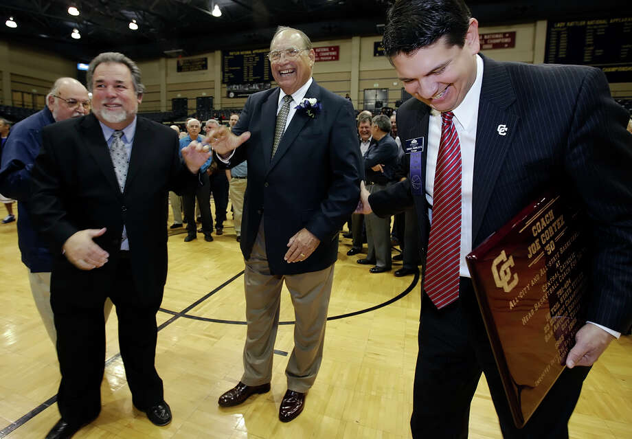 San Antonio Sports Hall of Fame inductee Joe Cortez (center) is congratulated by boys basketball head coach Romy Vela (left) and school principal Edward Ybarra during a halftime event honoring the longtime Central Catholic coach at the boys basketball game against Holy Cross at Greehey Arena at St. Mary's University on Feb. 9, 2010. Photo: Kin Man Hui, San Antonio Express-News / San Antonio Express-News