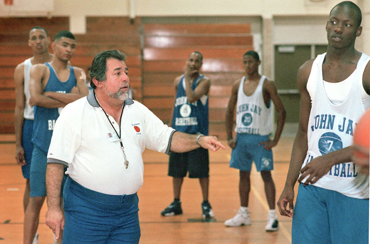 Coach Romy Vela is dwarfed by his players a Jay High School basketball practice in March 4, 2002, however he easily gets their full attention.