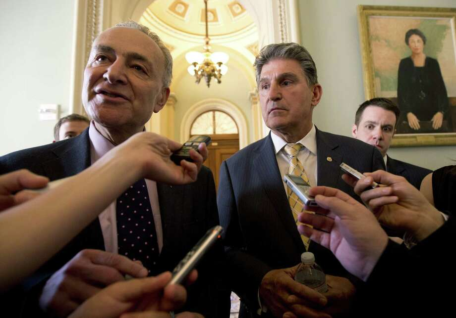 "Sens. Charles  Schumer, D-N.Y., (left) and Joe Manchin, D-W.Va., who says, ""This is a start. This is not the end of our work,"" speak to reporters on Capitol Hill. Photo: Manuel Balce Ceneta / Associated Press"