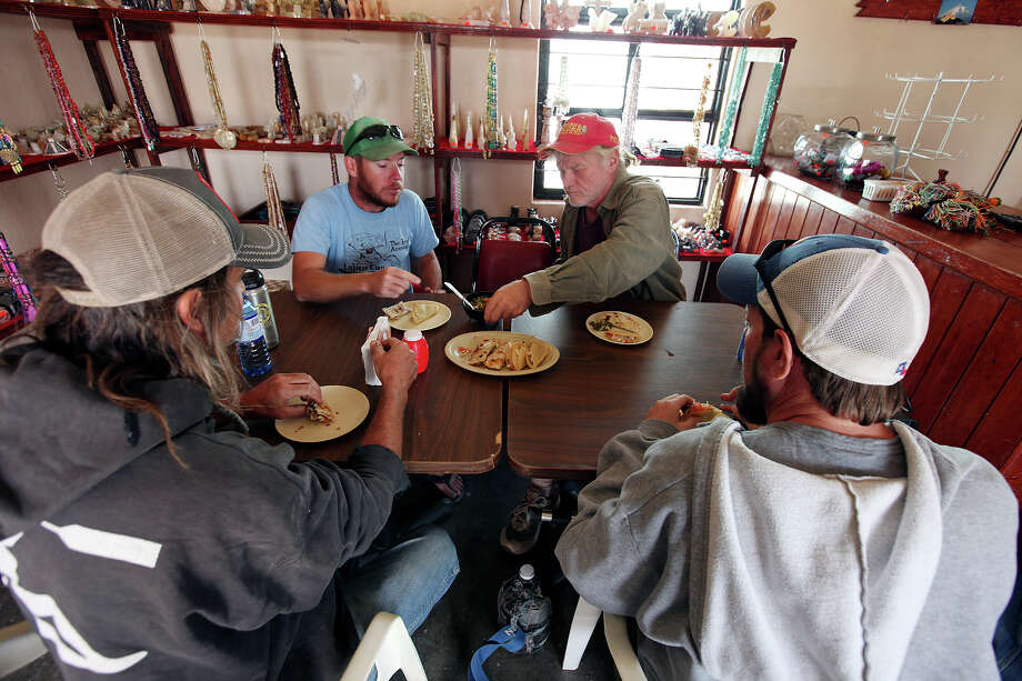 Visitors from Terlingua Zach Hubbard, 49 (from left), Billy Miller, 29, Jim Craig, 60, and Buckner Cook, 40, eat at Jose Falcon's Restaurant & Mexican Curios Shop Wednesday April 10, 2013 in Boquillas del Carmen, Mexico. Photo: Edward A. Ornelas, San Antonio Express-News / © 2013 San Antonio Express-News