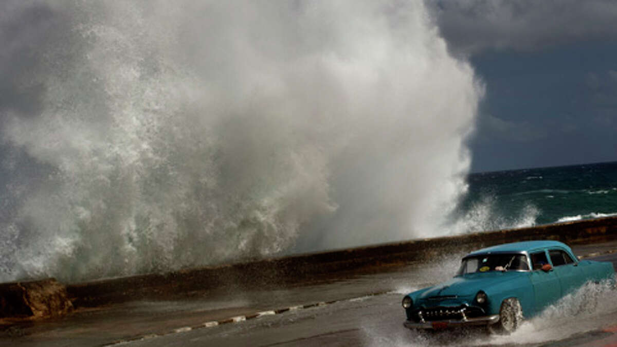 A driver maneuvers a car along a road in Havana, Cuba, during Hurricane Sandy last October. It later became the second costliest tropical system ever to hit the United States.