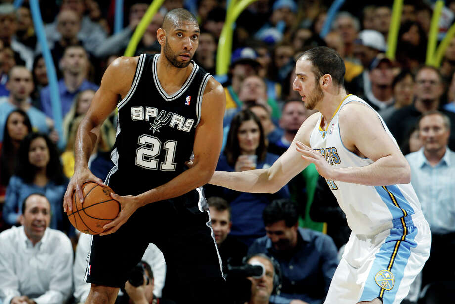 San Antonio Spurs center Tim Duncan (21) looks to pass the ball as Denver Nuggets forward Kosta Koufos defends in the first quarter of an NBA basketball game in Denver, Wednesday, April 10, 2013. Photo: David Zalubowski, Associated Press / AP