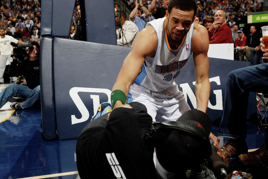 Denver Nuggets forward JaVale McGee checks on a television photographer after a collision while pursuing a loose ball out of play against the San Antonio Spurs in the first quarter of an NBA basketball game in Denver, Wednesday, April 10, 2013. Photo: David Zalubowski, Associated Press / AP