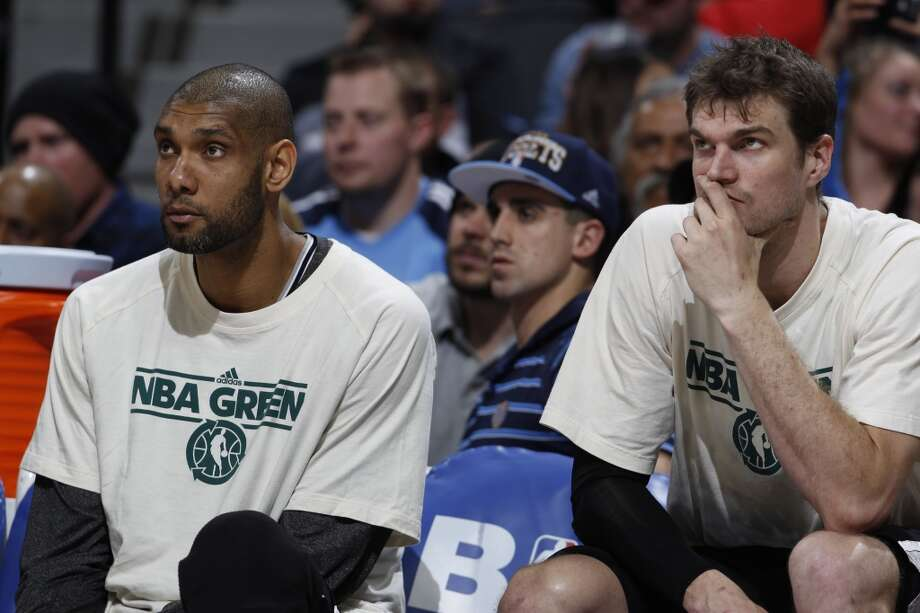San Antonio Spurs forwards Tim Duncan, left, and Tiago Splitter, of Brazil, look on from the bench as time runs out in the fourth quarter of the Denver Nuggets\' 96-86 victory over the Spurs in an NBA basketball game in Denver on Wednesday, April 10, 2013.