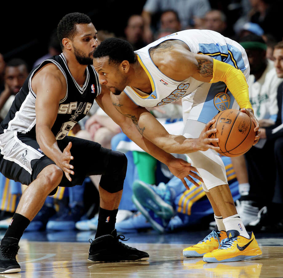 Denver Nuggets guard Andre Iguodala, right, picks up a loose ball as San Antonio Spurs guard Patty Mills, of Australia, covers in the fourth quarter of the Nuggets\' 96-86 victory in an NBA basketball game in Denver on Wednesday, April 10, 2013. Photo: David Zalubowski, Associated Press / AP