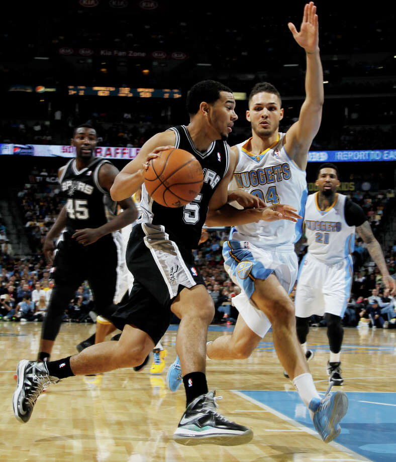 San Antonio Spurs guard Cory Joseph, left, drives for the basket as Denver Nuggets guard Evan Fournier, of France, covers in the third quarter of the Nuggets\' 96-86 victory in an NBA basketball game in Denver on Wednesday, April 10, 2013. Photo: David Zalubowski, Associated Press / AP