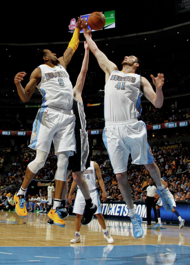 Denver Nuggets guard Andre Iguodala, left, and forward Kosta Koufos, right, team up to take the ball away from San Antonio Spurs forward Tiago Splitter, center, of Brazil, in the third quarter of the Nuggets\' 96-86 victory in an NBA basketball game in Denver on Wednesday, April 10, 2013. Photo: David Zalubowski, Associated Press / AP