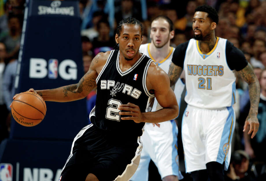San Antonio Spurs forward Kawhi Leonard (2) picks up a loose ball in front of Denver Nuggets forwards Wilson Chandler (21) and Kosta Koufos in the first quarter of an NBA basketball game in Denver, Wednesday, April 10, 2013. Photo: David Zalubowski, Associated Press / AP