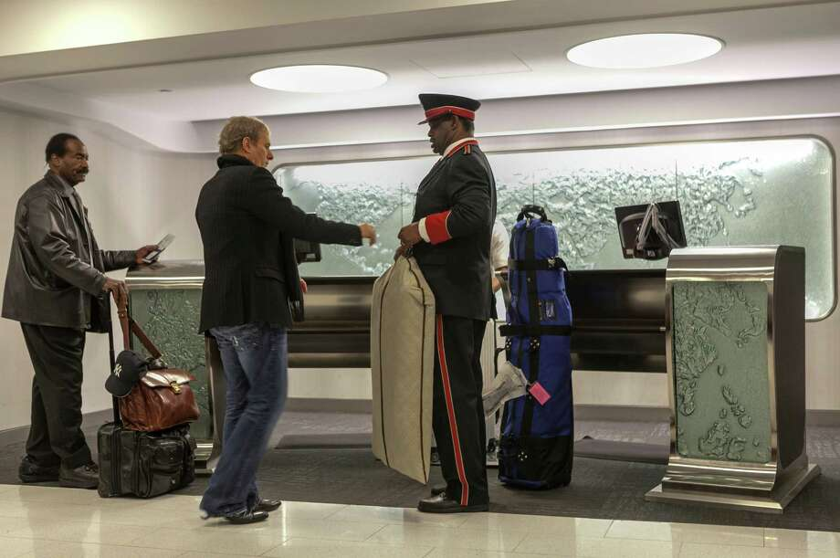 In this Thursday, March 14, 2013 photo,Singer and songwriter Michael Bolton, middle, is assisted by skycap Frederick Pearson, right, as he arrives at American Airlines Flagship Check-in terminal at Los Angeles International Airport, LAX. American's Flagship Check-in service, a VIP discreet and expedited check-in process offers personal access to agents for assistance with check-in and bag check, and a separate security line when flying through LAX and now Miami International Airport. Photo: Damian Dovarganes
